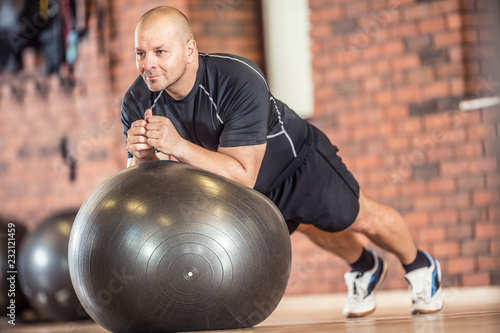 Wall mural Strong muscular man exercising with fitness ball facilities in gym or workout center