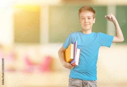Leinwanddruck Bild Cute little schoolgirl in glasses on blackboard background