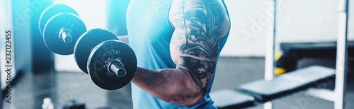 częściowy widok sportowca ćwiczeń z hantlami w siłowni