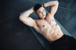 young asian sportsman with bare chest doing abs exercise on fitness mat at gym