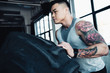 young asian sportsman flipping heavy tire at gym