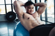 handsome young asian sportsman with bare chest doing abs exercise on fitness ball at gym