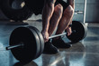 cropped view of muscular sportsman exercising with barbell at gym