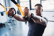 focused young muscular sportsman training with resistance bands in gym