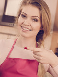Woman in apron pointing with finger - 232126003