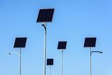 Street lighting works from solar panels, blue sky background. Before electricity transmission pylon. - 232126448