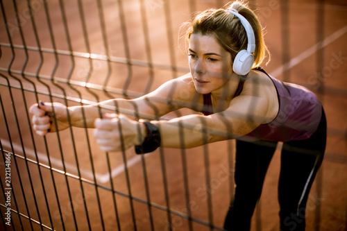 Leinwanddruck Bild Pretty young woman stretching during sport training