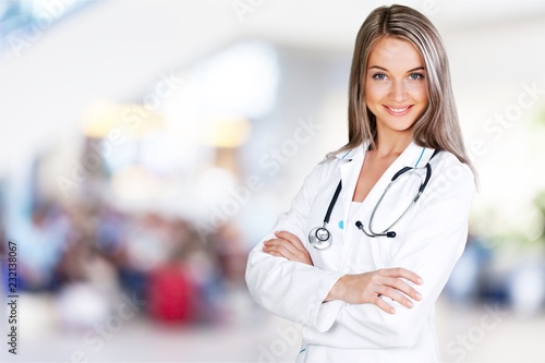 Leinwanddruck Bild Attractive young female doctor with blurred hospital