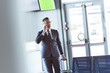 adult handsome businessman with smartphone and baggage walking at airport