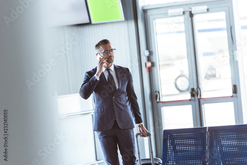 Foto Murales adult handsome businessman with smartphone and baggage walking at airport