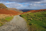 Path over the mountains through heather and bracken in warm Autumn orange colour under a blue and white cloudy sky, Lake District, UK - 232142244