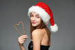 Closeup of beautiful girl in Santa hat holding Christmas candies composed in heart shape