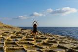 Femme faisant du yoga face à la mer - 232148477