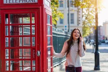 Weibliche reisende in London telefoniert mit ihrem Handy vor einer roten Telefonzelle, England