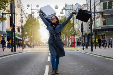 Modische, junge Stadt Frau mit Einkaufstaschen in der Hand auf der Oxford Street in London beim Shoppen