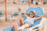 Young girl with sun glasses relaxing on stacked sunbeds on the beach - 232155623