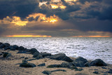 Cloudy sunset over a lake with rainy dark storm clouds and sunbeams and sun harps - 232159837