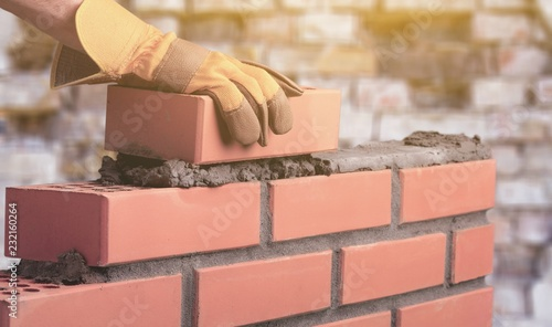 Foto Murales Worker builds a brick wall in the house
