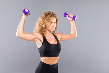 Sporty woman does the exercises with dumbbells on white background. Muscular woman in sportswear on white background. Strength and motivation. © F8studio