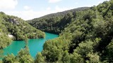Descending drone shot in a green valley with a stunning blue lake - 232166096