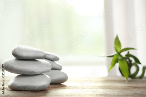 Leinwanddruck Bild Spa stones and bamboo leaves on table against blurred background. Space for text