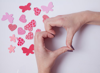 Female hand showing heart shape gesture. Isolated on white. `Happy Valentine's day