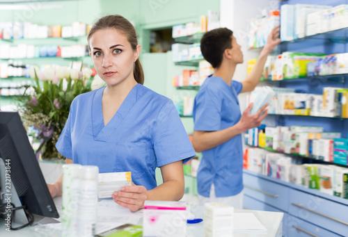 Leinwanddruck Bild Adult pharmacist is standing near cashbox