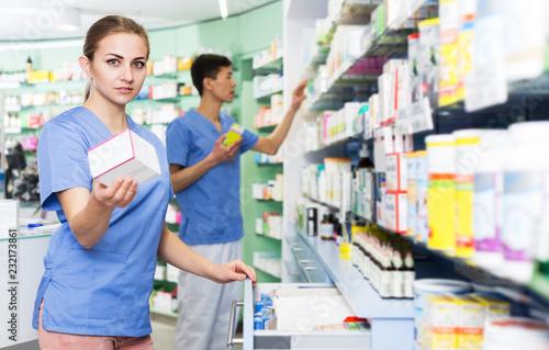 Leinwanddruck Bild Pharmacist looking medicines in lockers