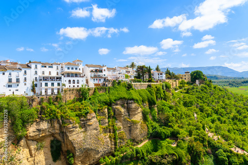 Leinwanddruck Bild White houses on green hills in Ronda village in spring, Andalusia, Spain
