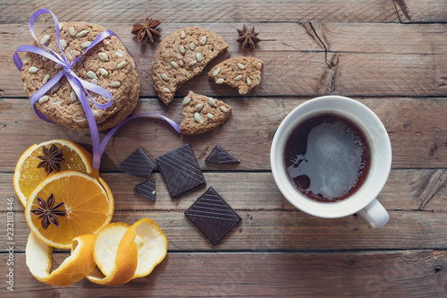 cup with espresso, oatmeal cookies, tied with a ribbon, orange with raisin and chocolate