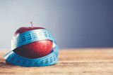 red apple with blue measuring tape