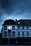 Mansion with illuminated windows at dusk. - 232194001