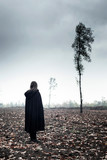 Woman in black cape in moody countryside. - 232194004