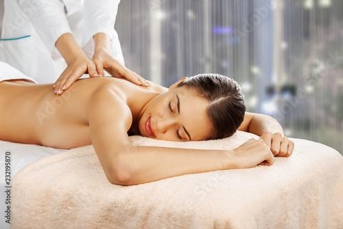 Leinwanddruck Bild Beautiful young woman relaxing with massage at