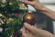 Retro image of female hands hanging shiny brown holiday bauble - 232205260