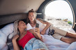 Wake up. Young couple of good-looking travelers waking up in their compact trailer in the morning