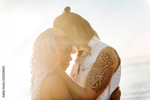 Foto Murales Sunrise and hugs. Loving cute couple feeling extremely happy while watching the sunrise and hugging