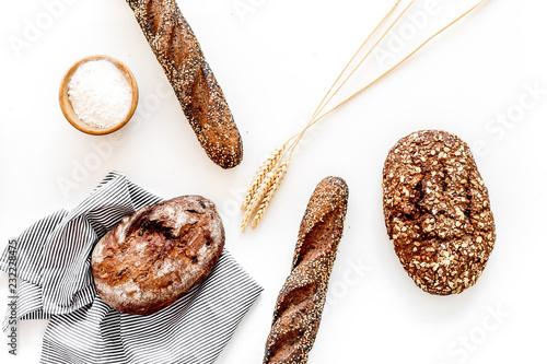 Foto Murales Brown bread. Fresh rustic homemade bread and loaf on tablecloth decorated with ears and flour on white wooden background top view