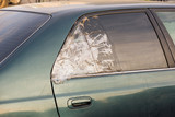 broken dark car rear window sealed with scotch tape - 232228820