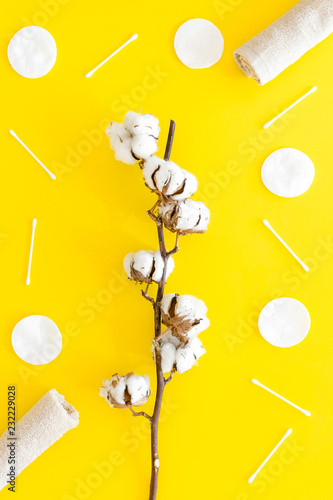 Leinwanddruck Bild Cotton hygiene products. Cotton pads and swabs, towels twisted coil near dry cotton flowers on yellow background top view