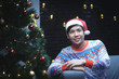 Asian Man With Christmas Costume Sitting Beside Christmas Tree