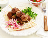 Lamb kebabs on skewers with onion and buttermilk sauce. - 232233053