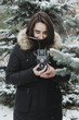 Lifestyle portrait of young adult female holding vintage film camera and making picture of nature outdoors in winter woods, selective focus