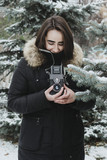 Lifestyle portrait of young adult female holding vintage film camera and making picture of nature outdoors in winter woods, selective focus - 232234068