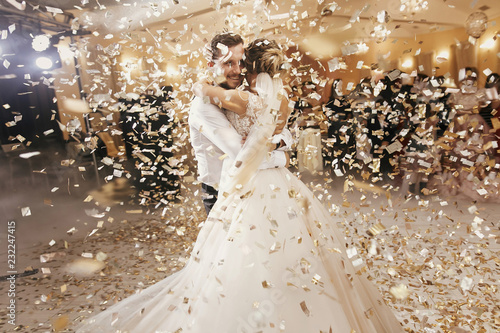 Gorgeous bride and stylish groom dancing under golden confetti at wedding reception. Happy wedding couple performing first dance in restaurant. Romantic moments - 232247415