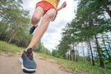 Closeup of athlete's feet running at the park. Fitness woman jogging outdoors. Exercising on forest path. Healthy, fitness, wellness lifestyle. Sport, cardio, workout concept
