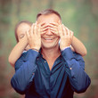 Cute little girl covering eyes of her father outdoors. Daughter makes surprise to her dad