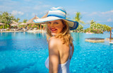 Portrait of woman wearing summer hat in resort on vacation - 232254048