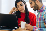 Young Arab couple sitting in front of the laptop working in the office. - 232267064