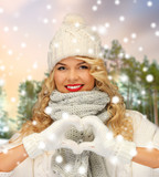 people, season and leisure concept - happy woman in hat, scarf and mittens showing hand heart over winter forest background - 232268000